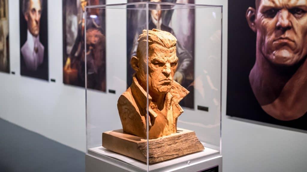 In primo piano, un busto di terracotta in  una teca. Sullo sfondo diversi quadri. I soggetti sono legati a Dishonored