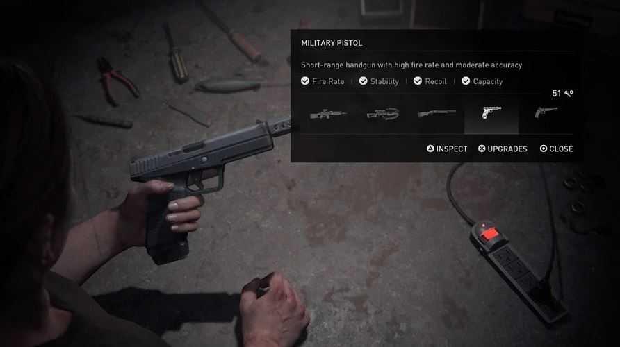 Ellie con in mano una pistola militare