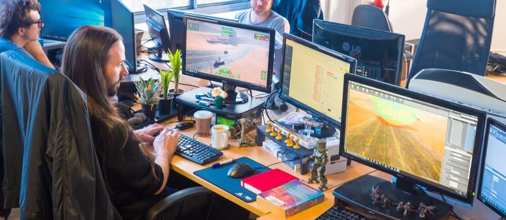 Uno sviluppatore sta creando un gioco davanti al suo PC e i suoi monitor