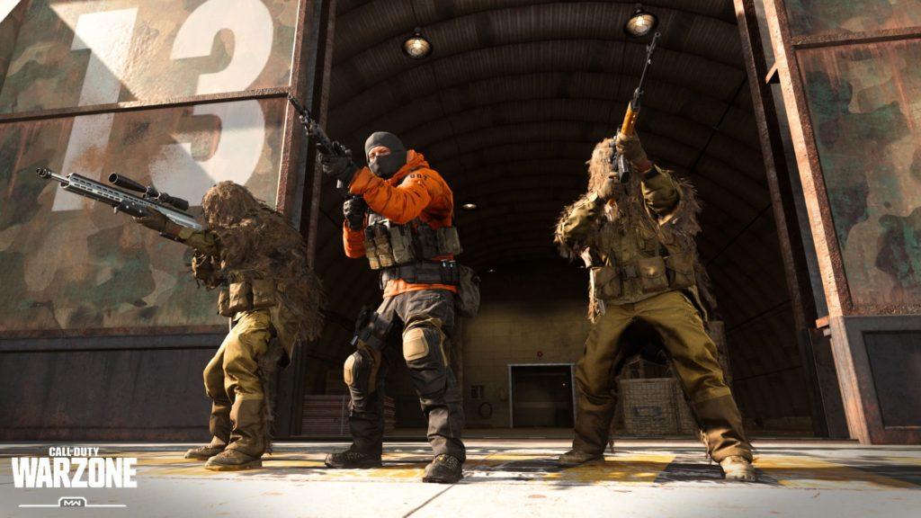 Tre operatori di Warzone con armi spianate fuori ad un hangar