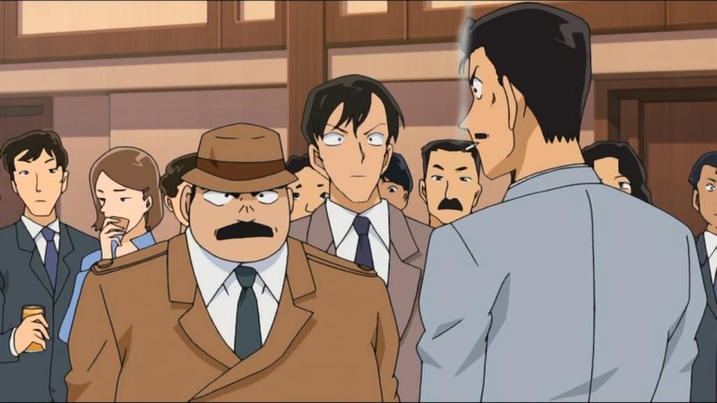 L'ispettore capo Juzo Megure e l'ispettore Magoro Akechi stanno discutendo di un caso. Magoro sta fumando una sigaretta